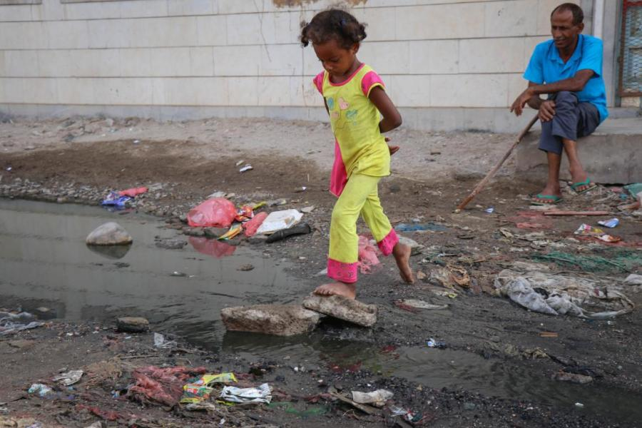 A girl is trying hard to cross through the sewage drain
